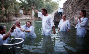 Christian Pilgrims participating in a group baptismal ritual in the river Jordan