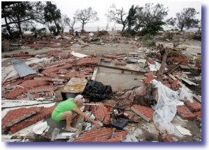 Woman picks through the rubble of her home after Hurricane Katrina